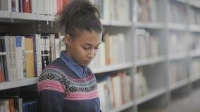 Portret piękny amerykanin afrykańskiego pochodzenia żeńskiego ucznia obsiadanie na podłodze w szkolnej bibliotece