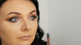 Portret piękny błękitnooki kobieta model z długim czarni włosy który robi wieczór brązu oka brwi i makeup zbiory wideo