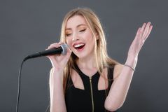 Portret piękny blondynki młodej kobiety śpiew w micropho Zdjęcia Stock