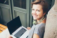 Portret piękny caucasian kobiety blogger z laptopu obsiadaniem w ulicznej kawiarni relaksował w świeżym powietrzu Zdjęcie Stock
