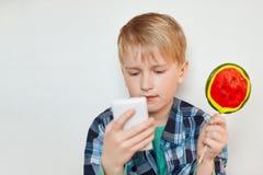 Portret piękny chłopiec oblizania lizak koncentruje spojrzenie podczas gdy używać telefonu komórkowego czytelniczego ebook lub ba Obraz Royalty Free