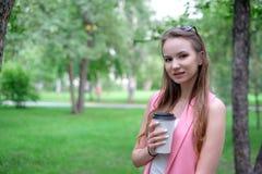 Portret piękny dziewczyny odprowadzenie na parku Utrzymywać takeaway napój w jeden ręce Fotografia Stock