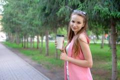 Portret piękny dziewczyny odprowadzenie na parku Utrzymywać takeaway napój w jeden ręce Zdjęcia Royalty Free