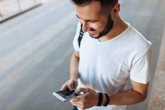 Portret piękny elegancki facet patrzeje telefon na ulicie, przeciw budynku tłu, może używać dla advertisi zdjęcie stock