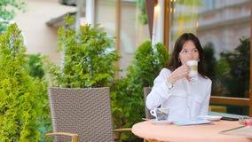 Portret piękny kobiety obsiadanie w plenerowy cukiernianym pijący kawowego i używa smartphone Młodej dziewczyny przyglądający ins zbiory