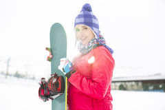 Portret piękny młodej kobiety mienia snowboard w śniegu Obraz Royalty Free