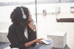 Portret piękny młody ładny amerykanin afrykańskiego pochodzenia dziewczyny obsiadanie na i słuchanie muzyka w ona jeziorze lub pl obrazy stock