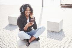 Portret piękny młody ładny amerykanin afrykańskiego pochodzenia dziewczyny obsiadanie na i słuchanie muzyka w ona jeziorze lub pl obraz stock