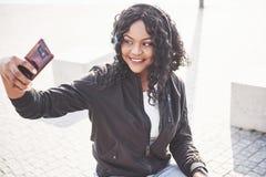 Portret piękny młody ładny amerykanin afrykańskiego pochodzenia dziewczyny obsiadanie na i słuchanie muzyka w ona jeziorze lub pl zdjęcia royalty free