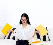Portret piękny młody żeński uczeń z no chcieć czyta książkę na kanapie w żywym pokoju Zdjęcie Stock