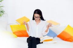 Portret piękny młody żeński uczeń z no chcieć czyta książkę na kanapie w żywym pokoju Fotografia Stock
