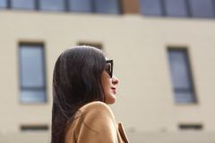 Portret piękny młody bizneswoman plenerowy nad zamazanym ulicznym tłem Profil elegancka brunetki kobieta, jest ubranym beż zdjęcia stock