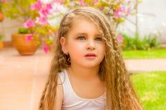 Portret piękny małej dziewczynki preschool obsiadanie na ziemi pozuje dla kamery, w ogrodowym tle obraz stock
