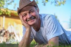 Portret piękny starsza osoba mężczyzna Kłama na trawie uśmiechniętej i patrzeje kamerę fotografia stock