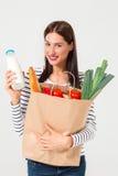 Portret piękny uśmiechnięty kobiety mienie robi zakupy papierową torbę z organicznie świeżą żywnością odizolowywającą na białym t Zdjęcia Royalty Free