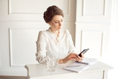 Portret piękny uśmiechnięty młody brunetka bizneswoman w białym koszulowym obsiadaniu na jaskrawej nowożytnej stacji roboczej obraz royalty free