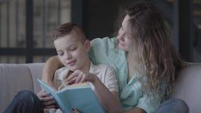 Portret pięknych potomstw macierzysty czytanie książka jej piękny syna obsiadanie na kanapie bractwo rodzina zbiory