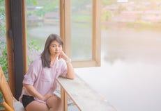 Portret pi?kna azjatykcia kobieta siedzie? na drewnianym krze?le st?? blisko okno zdjęcie stock