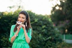 Portret piękna brunetki dziewczyna w zieleni sukni, je cukierek lubi pandy Fotografia Stock