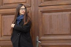 Portret piękna dziewczyna na tle wielki drewniany drzwi Fotografia Royalty Free