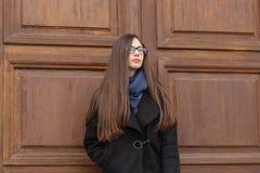 Portret piękna dziewczyna na tle wielki drewniany drzwi Obraz Stock