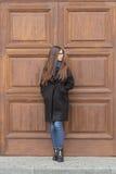 Portret piękna dziewczyna na tle wielki drewniany drzwi Obrazy Stock