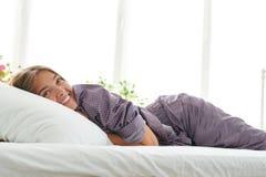 Portret piękna dziewczyna w piżamach cieszy się ranku lying on the beach zdjęcia royalty free
