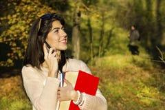 Portret piękna kobieta opowiada na telefonie w parku Obrazy Royalty Free