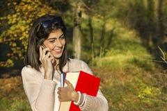 Portret piękna kobieta opowiada na telefonie w parku Fotografia Royalty Free