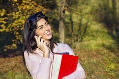 Portret piękna kobieta opowiada na telefonie w parku Zdjęcie Royalty Free