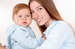 Portret piękna mama i jej dziecko w sypialni Zdjęcia Stock