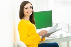 Portret pi?kna u?miechni?ta kobieta pracuje na jej biurku z ziele? ekranem w biurowym ?rodowisku, zdjęcie stock