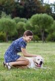 Portret piękny kobiety obsiadanie na trawie z playfu Zdjęcia Royalty Free