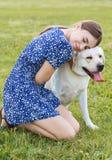 Portret piękny kobiety obsiadanie na trawie z playfu Fotografia Stock