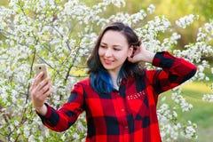 Portret pi?kny m?odej kobiety selfie w parku z smartphone zdjęcie royalty free