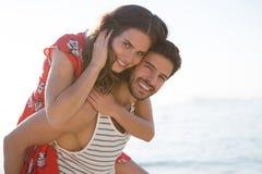 Portret piggybacking jego dziewczyny przy plażą uśmiechnięty młody człowiek Obraz Stock