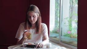 Portret pije i patrzeje w telefonie herbaciany młoda kobieta zdjęcie wideo