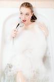 Portret piosenka & zdrój: powabna blond młoda kobieta ma zabawę relaksuje w skąpaniu z piankowym śpiewackim szczęśliwym uśmiechem Obrazy Stock