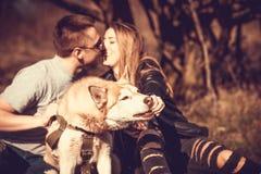 Portret plenerowy z całowanie parą behind husky pies Obrazy Royalty Free