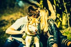 Portret plenerowy z całowanie parą behind husky pies Zdjęcie Royalty Free