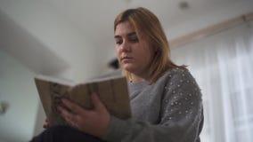 Portret plus de zitting van het de lezingsboek van het groottemeisje bij bank in huis Het mollige boek van de vrouwenholding in h stock videobeelden