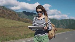 Portret podróżnik kobiety zakończenie turystyczna dziewczyna z papierową mapą w jej rękach chodzi wzdłuż autostrady zbiory wideo