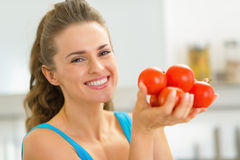 Portret pokazuje pomidoru szczęśliwa młoda kobieta Obraz Stock