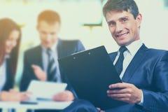 Portret pomyślny biznesmen w biurze na tło biznesu pracującej drużynie w nowożytnym Obrazy Royalty Free