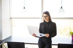 Portret pomyślny bizneswomanu mienia laptop w ona ręki Szczęśliwa piękna ufna kobiety pozycja przy biurem z notatnikiem Zdjęcia Royalty Free