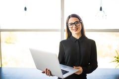 Portret pomyślny bizneswomanu mienia laptop w ona ręki Szczęśliwa piękna ufna kobiety pozycja przy biurem z notatnikiem Zdjęcie Royalty Free