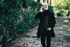 Portret pomyślny wieka średniego biznesmen opowiada na jego smartphone podczas gdy chodzący w miasto parku Horyzontalny, zamazany Zdjęcia Stock
