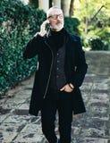 Portret pomyślny wieka średniego biznesmen opowiada na jego smartphone podczas gdy chodzący w miasto parku Vertical, zamazujący Obraz Royalty Free