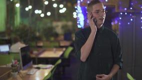 Portret pomyślny zadawalający urzędnik opowiada na telefonie komórkowym podczas gdy stojący blisko jego miejsce pracy w nowożytny zbiory wideo