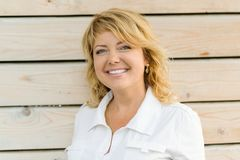 Portret positief rijp vrouw het glimlachen close-up op middelbare leeftijd Blondevrouw, openlucht houten achtergrond stock foto